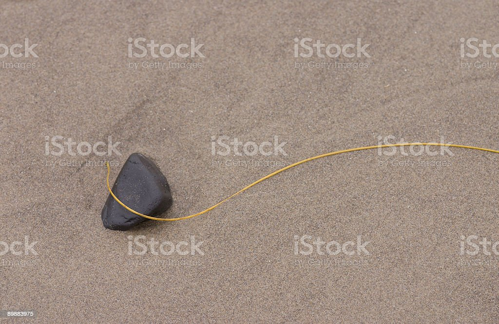 beach stone entangled in grass royalty-free stock photo