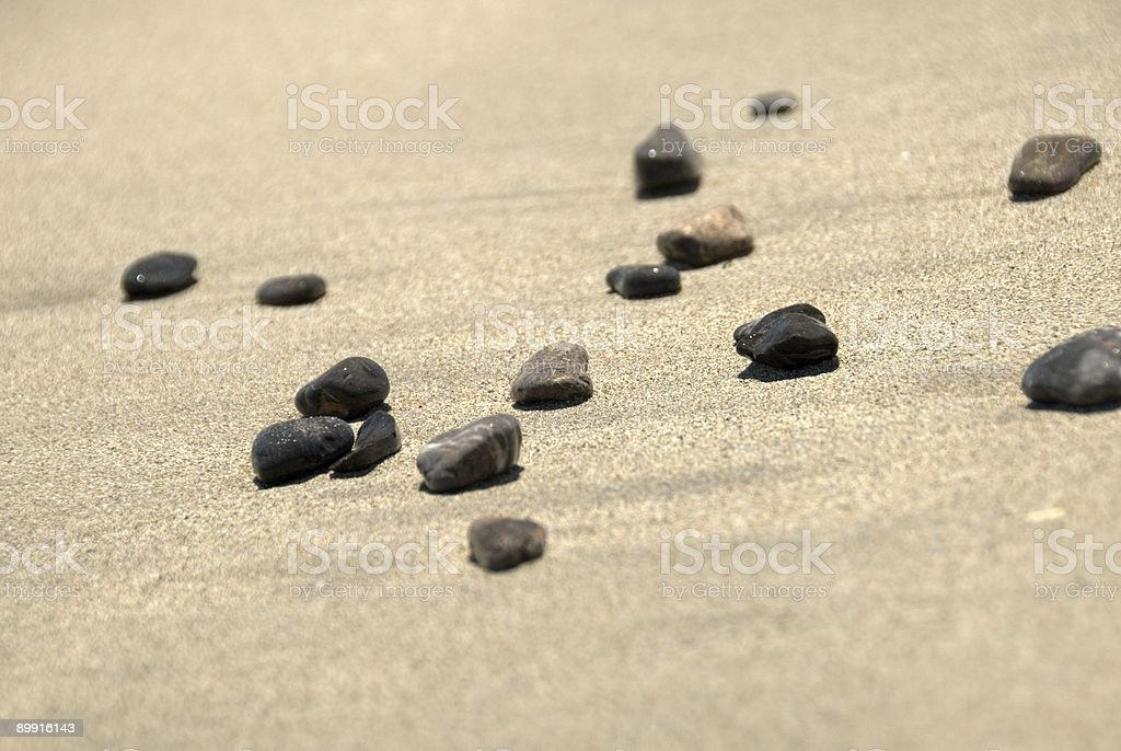 Beach stones (pebbles) on a sand stock photo