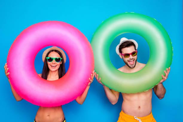 beach stil! resor daydream koncept. positiv tjej och stilig man ser genom färgglada gummiringar njuter resten isoleras på blå bakgrund - inflatable ring bildbanksfoton och bilder