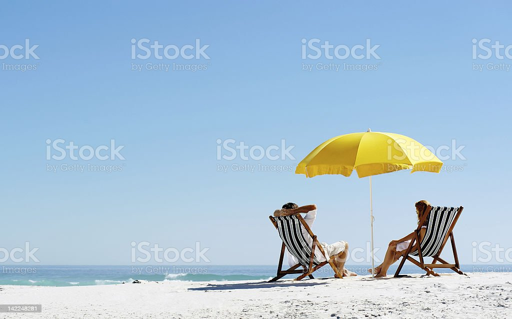 Beach summer couple on island vacation holiday relax in the sun on...