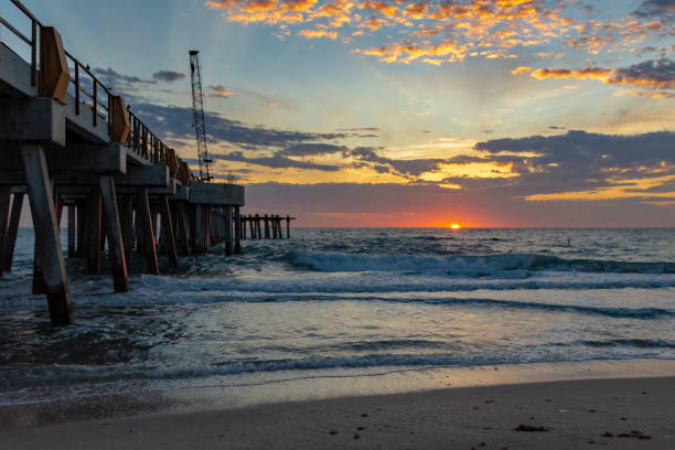 beach sunrise by a fishing peir under construction stock photo