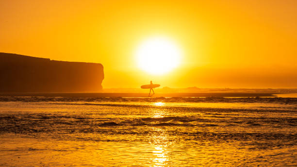 Beach Sunset with silhouette of a surfer carrying a surfboard stock photo