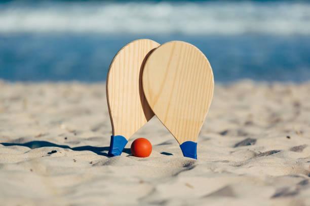 beach tennis, beach paddle ball, matkot. beach rackets and ball on the beach - set tennis o pallavolo foto e immagini stock
