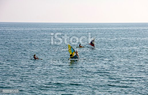 Budva, Montenegro - September 2, 2015: People surfing on adriatic sea with view of Stari Grad (Old Town) Budva, Montenegro. People are relaxing on the beach near the Old town in the popular resort of Budva.