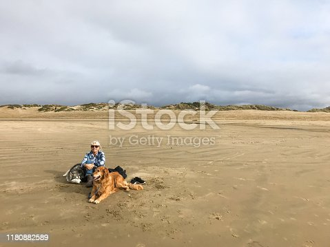 A child plays, learns, and finds animals in the surf along with his dog and grandmother.