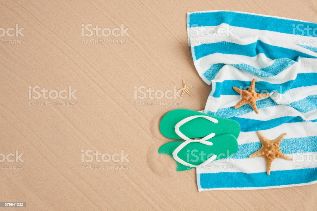 Striped towel and flip-flops on ocean sand. Beach holiday background...
