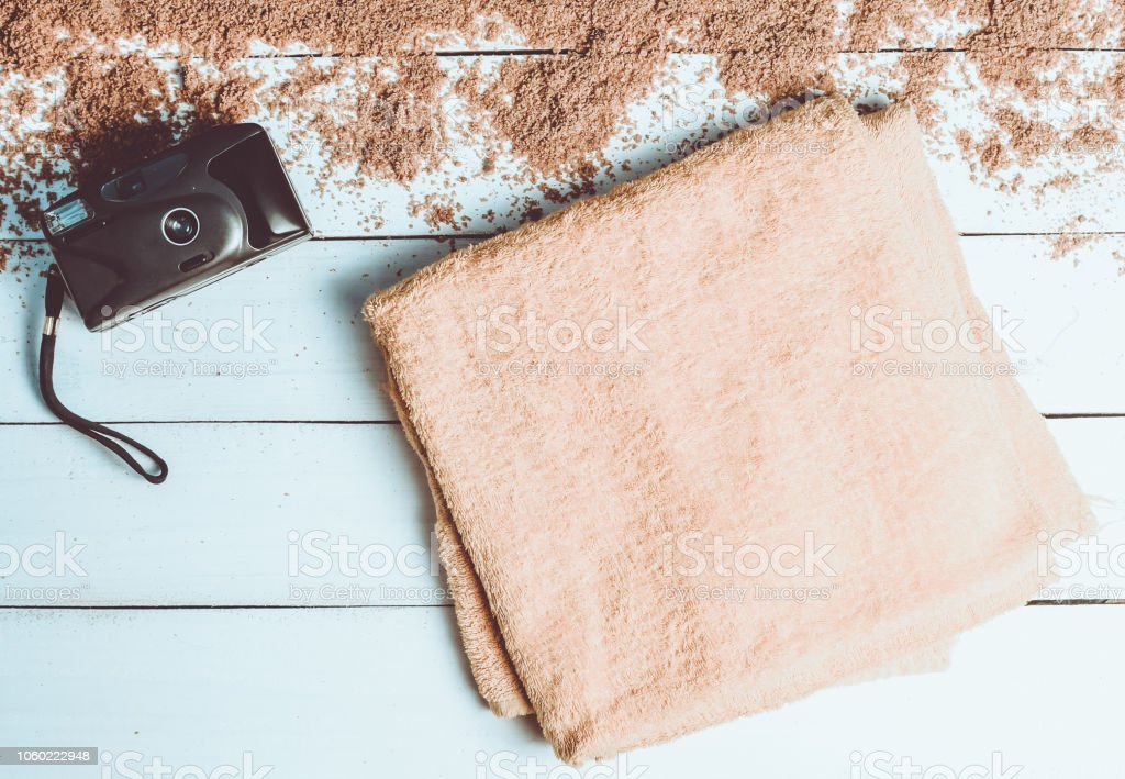 A beach towel and vintage camera on a white wooden surface. The...