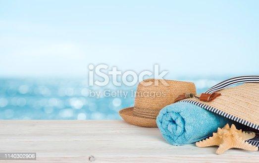 Beach towel, bag and hat on wood over defocused ocean