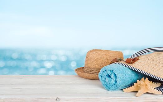 istock Beach towel, bag and hat on wood over defocused ocean 1140302906