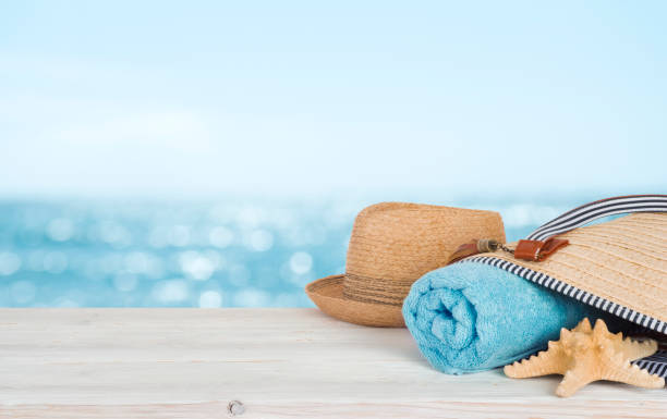 Beach towel, bag and hat on wood over defocused ocean stock photo