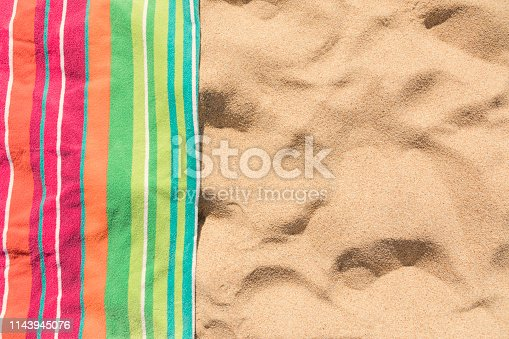 Beach towel on sandy tropical beach top view with copy space