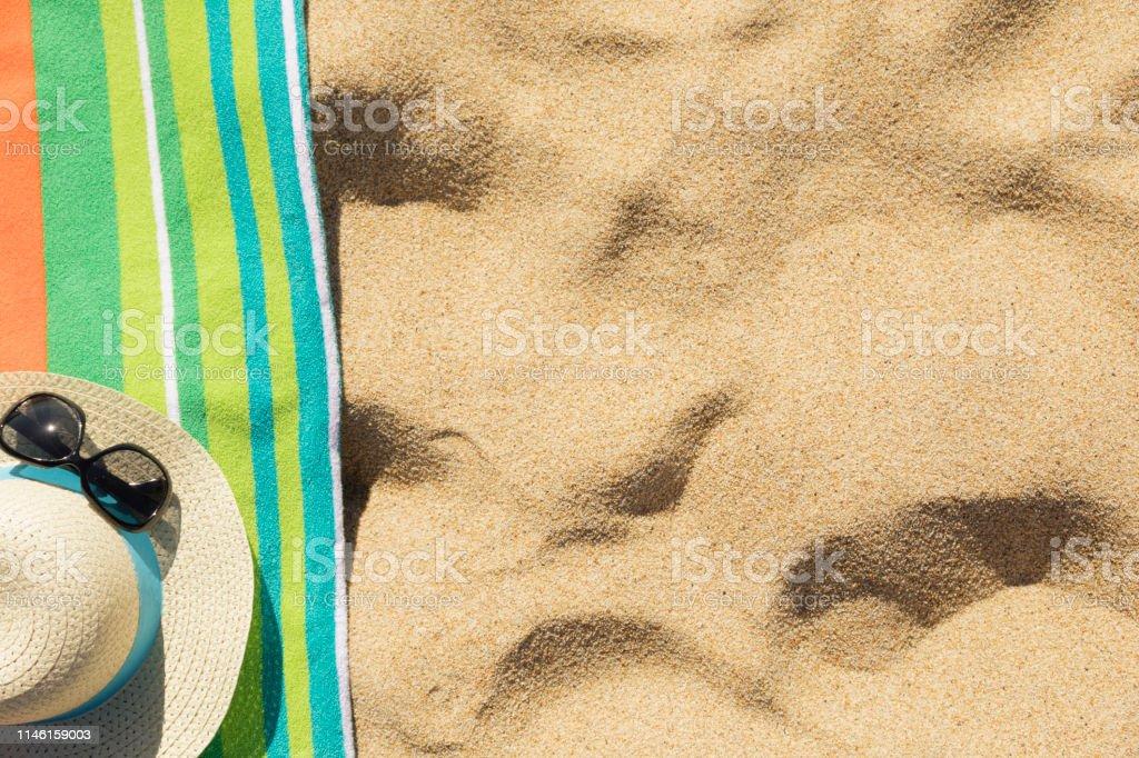 Beach towel with beach accessories on sandy tropical beach top view...