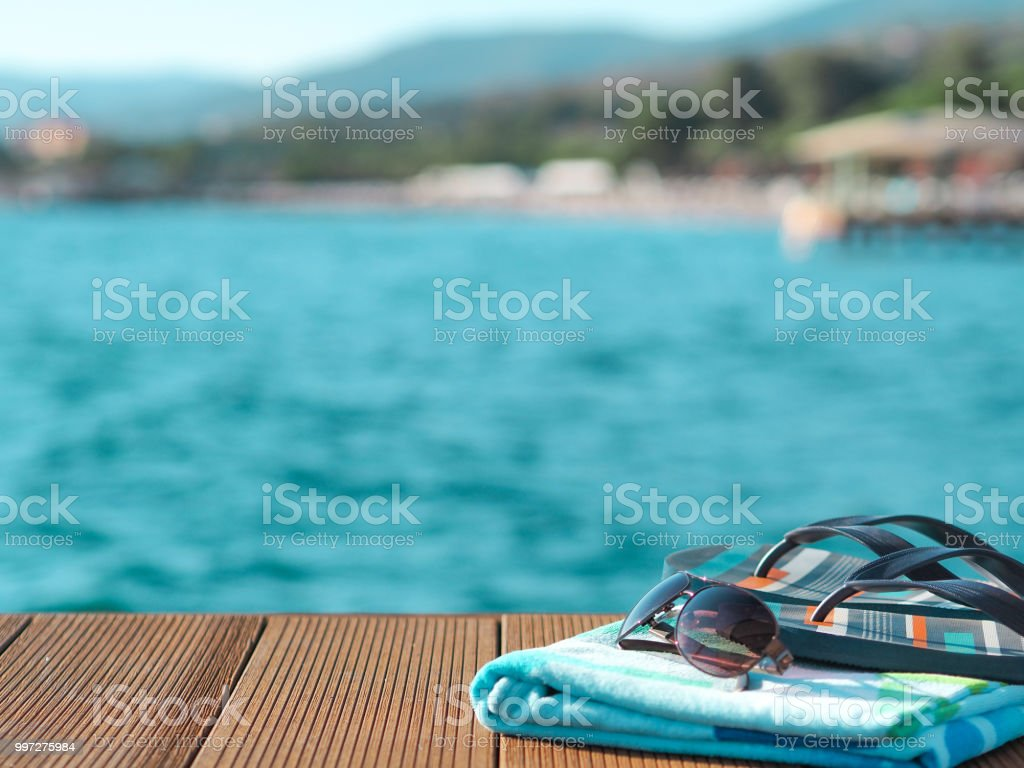 beach towel, sunglasses and slippers on the beach pier