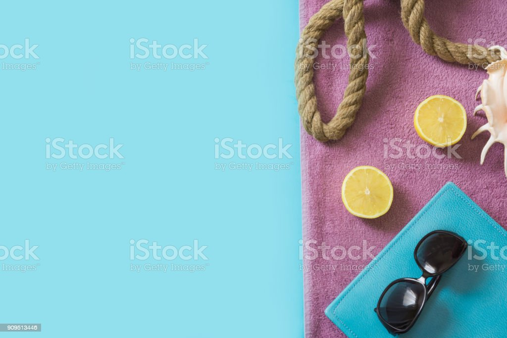 Beach towel, sunglasses and summer accessories on blue. Travel concept. Blank mock up for advertising or packaging. stock photo