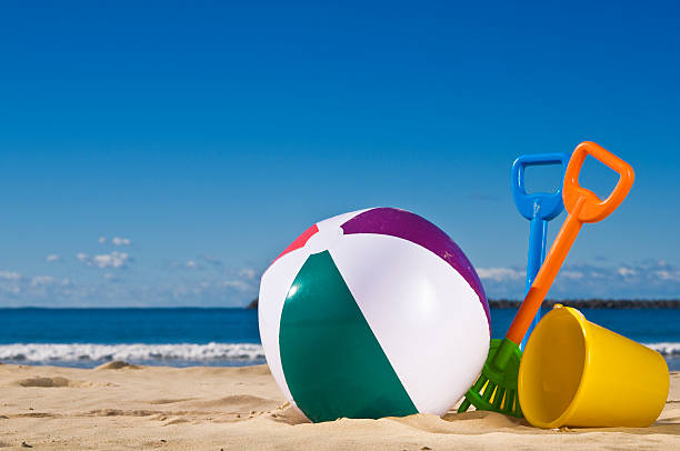 beach toys sitting on the beach - beach ball stock photos and pictures