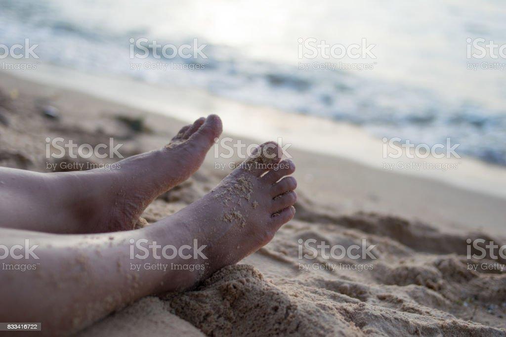 Beach travel - woman legs on sand beach. Travel concept. stock photo