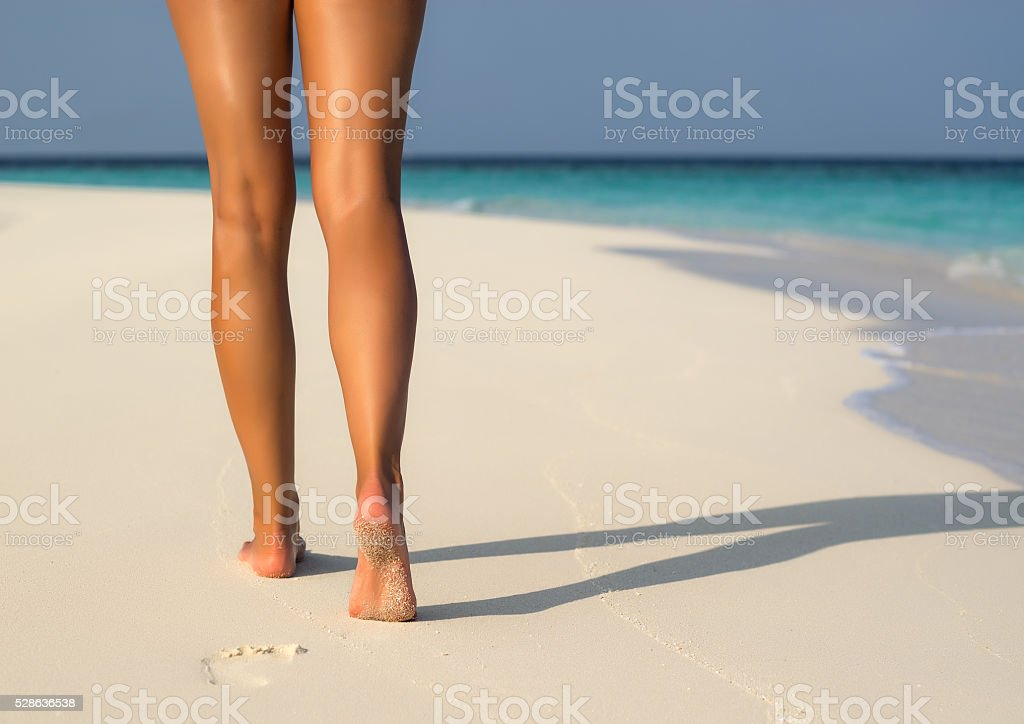 Beach travel - woman walking on sand beach leaving footprints stock photo