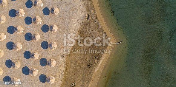istock beach umbrella, aerial view, beach and sea 1162178184