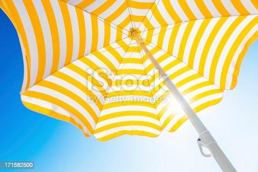 Beach umbrella against blue morning sky.