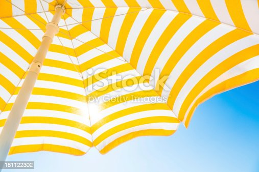 Beach umbrella against blue morning sky.