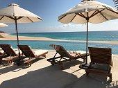 Beach umbrella  Deck chair infinity pool blue ocean