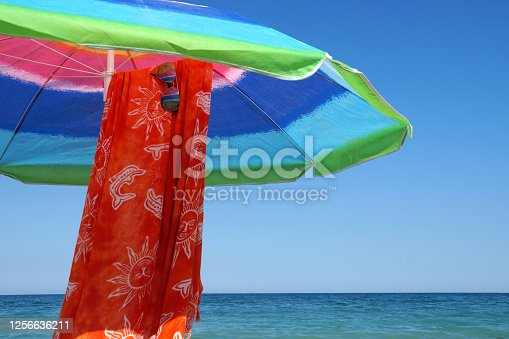 beach umbrella, pareo and sunglasses against the sea horizon and clear sky, copy space.
