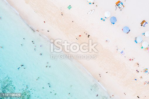 931756010 istock photo Beach umbrellas and blue ocean. Beach scene from above. People relaxing on Melasti beach, Bali. 1141196429