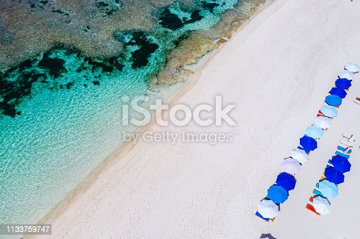 931756010 istock photo Beach umbrellas and blue ocean. Beach scene from above 1133759747