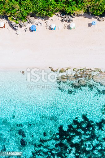 931756010 istock photo Beach umbrellas and blue ocean. Beach scene from above 1133990887