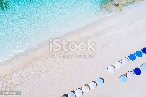 931756010 istock photo Beach umbrellas and blue ocean. Beach scene from above 1135304197