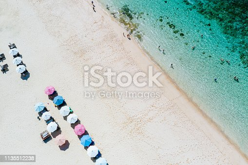 931756010 istock photo Beach umbrellas and blue ocean. Beach scene from above 1135512238