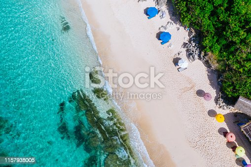 931756010 istock photo Beach umbrellas and blue ocean. Beach scene from above 1157938005
