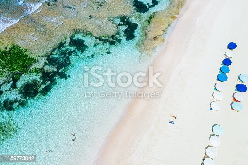 931756010 istock photo Beach umbrellas and blue ocean. Beach scene from above 1159773042