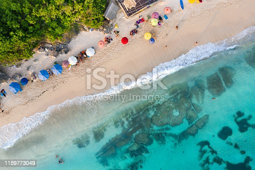 931756010 istock photo Beach umbrellas and blue ocean. Beach scene from above 1159773049