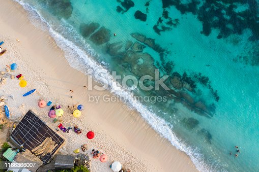 931756010 istock photo Beach umbrellas and blue ocean. Beach scene from above 1166366007
