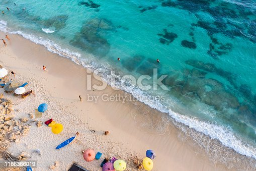 931756010 istock photo Beach umbrellas and blue ocean. Beach scene from above 1166366019