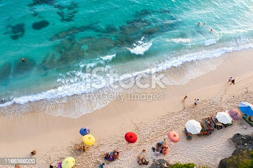 931756010 istock photo Beach umbrellas and blue ocean. Beach scene from above 1166366020