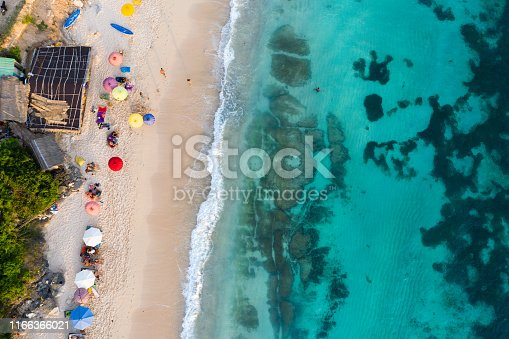 931756010 istock photo Beach umbrellas and blue ocean. Beach scene from above 1166366021