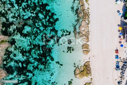 931756010 istock photo Beach umbrellas and blue ocean. Beach scene from above 1185884339