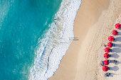 Beach scene - turquoise transparent ocean and red beach umbrellas on white sand beach. Bali, Dreamland beach aerial view.