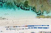 Beach scene - turquoise transparent ocean and colourful beach umbrellas on white sand beach. Bali, Melasti beach aerial view.