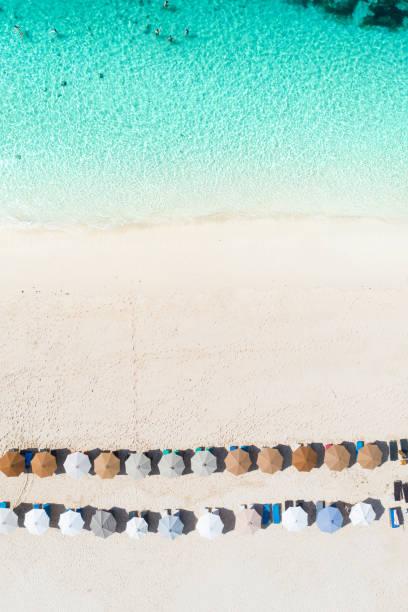 Beach umbrellas and blue ocean. Beach scene from above stock photo