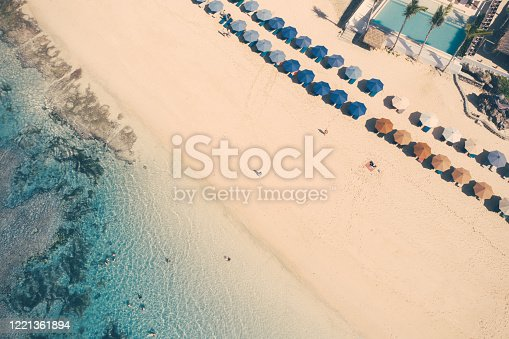 931756010 istock photo Beach umbrellas and blue ocean. Beach scene from above 1221361894