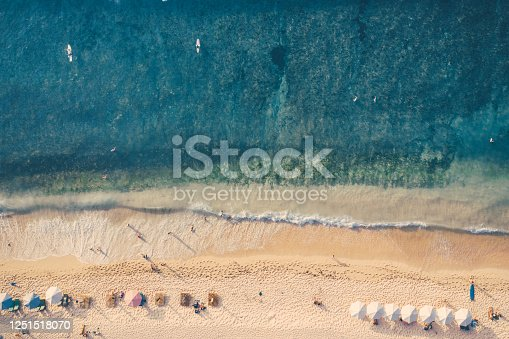 931756010 istock photo Beach umbrellas and blue ocean. Beach scene from above 1251518070