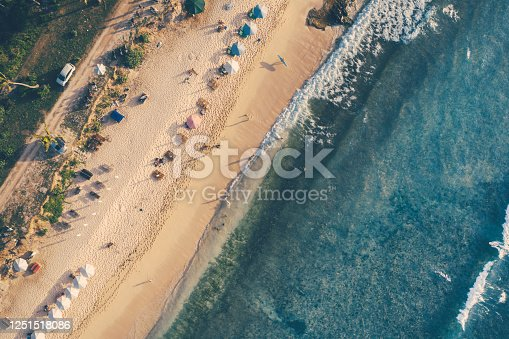 931756010 istock photo Beach umbrellas and blue ocean. Beach scene from above 1251518086