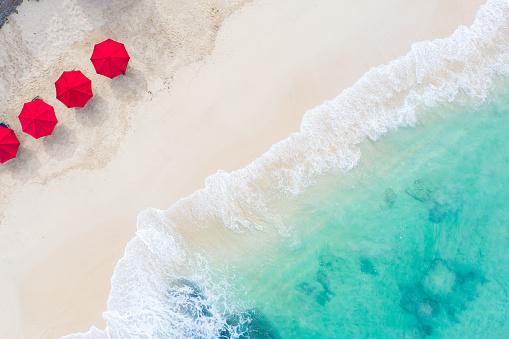 Beach scene - turquoise transparent ocean and red beach umbrellas on white sand beach. Bali beach aerial view.