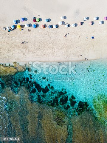 931756010 istock photo Beach umbrellas and blue ocean. Beach scene from above 931756004