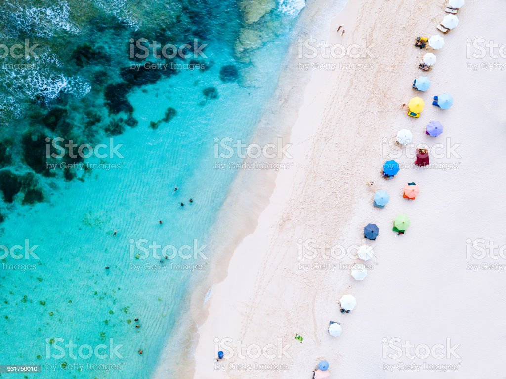 Beach umbrellas and blue ocean. Beach scene from above stock photo