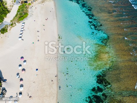 931756010 istock photo Beach umbrellas and blue ocean. Beach scene from above 971400380