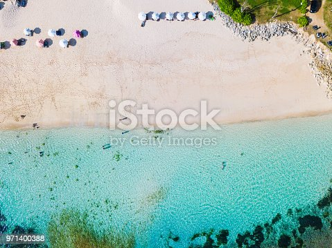 931756010 istock photo Beach umbrellas and blue ocean. Beach scene from above 971400388